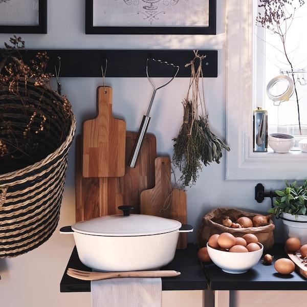 Blat kuchenny zapełniony misakami, garnkiem i dekami do krojenia.