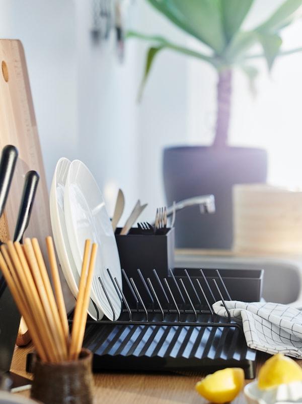Blat z mnóstwem akcesoriów kuchennych, między innymi kubkiem z pałeczkami i czarną suszarką do naczyń RINNIG, a także dwoma połówkami cytryny.