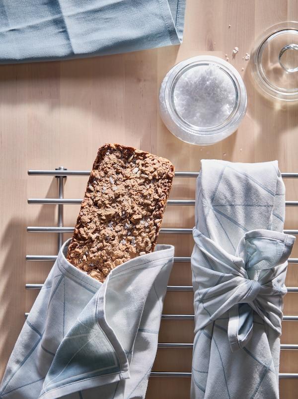 Blat ze szklanym słoikiem pełnym soli i dwa bochenki wieloziarnistego chleba zawinięte w ręczniki kuchenne SANDVIVA i ułożone na podstawce LÄMPLIG.