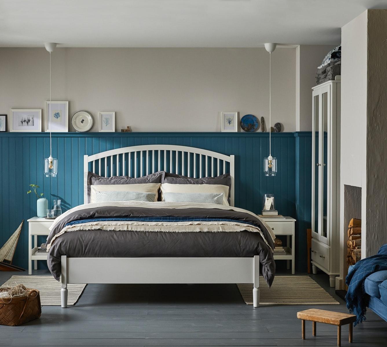 Blau-weißes Schlafzimmer mit weißem Ablagetisch, Kleiderschrank und Hängeleuchtenschirm.