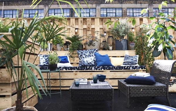 Blaue Kissen und Möbel für draussen auf einer Dachterrasse, u. a. mit STOCKHOLM 2017 Meterware Karos/blau.