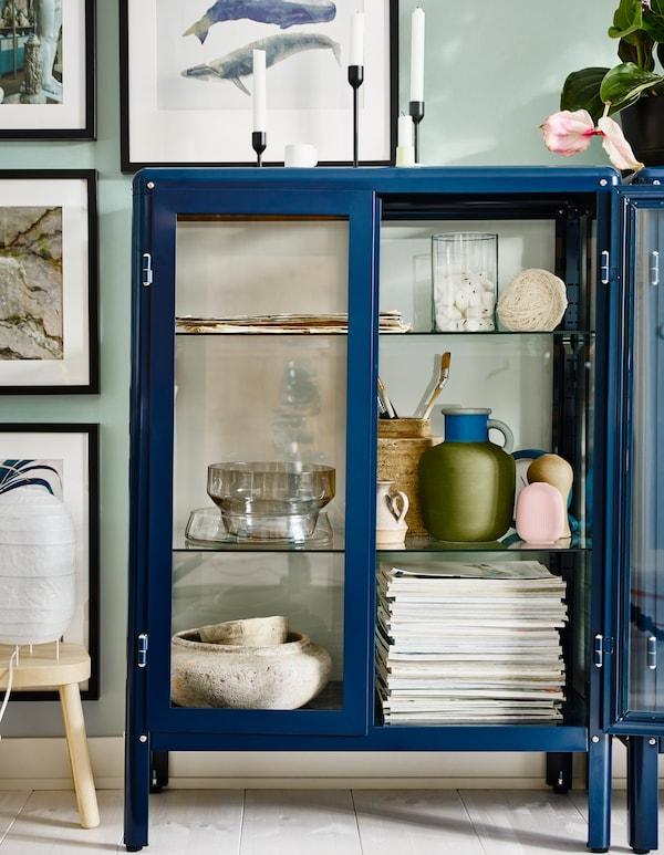 Blauwe IKEA FABRIKÖR vitrinekast met verstelbare planken wordt gebruikt om glaswerk en souvenirs uit te stallen en te beschermen.