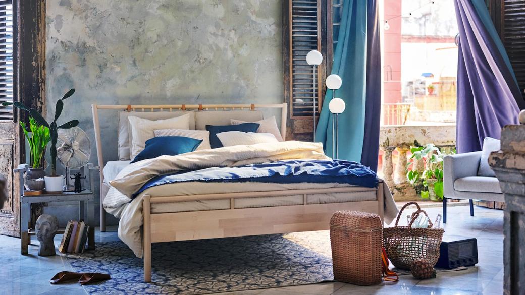 Blauwgrijze slaapkamer met turkooizen en paarse verduisterende gordijnen waar de wind mee speelt.