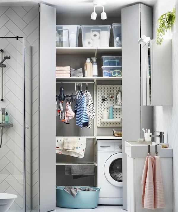Blick durch eine graue Tür auf einen Waschbereich, u. a. mit SKÅDIS Lochplattenkombination in Weiß, auf Waschmaschine, Wäschetrockner und Boxen auf Regalen.