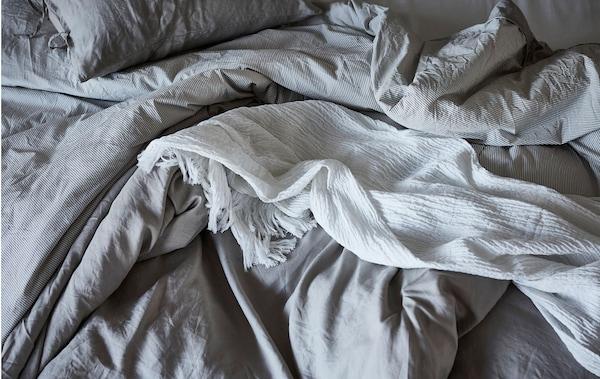 Blick von oben auf ein benutztes Bett mit verknitterter, flauschiger, einfarbiger Bettwäsche; eine Tagesdecke liegt achtlos oben drauf.