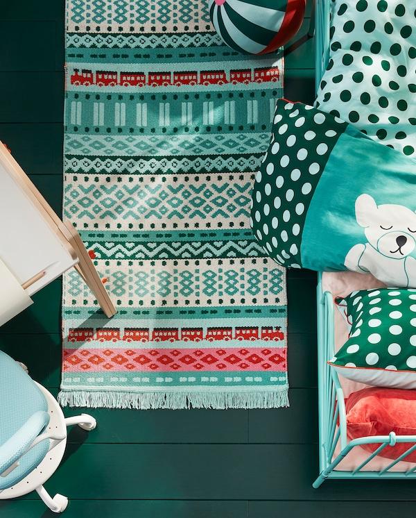Blick von oben auf ein KÄPPHÄST Stoffspielzeug, einen Teppich und Bettwäsche in bunten Farben