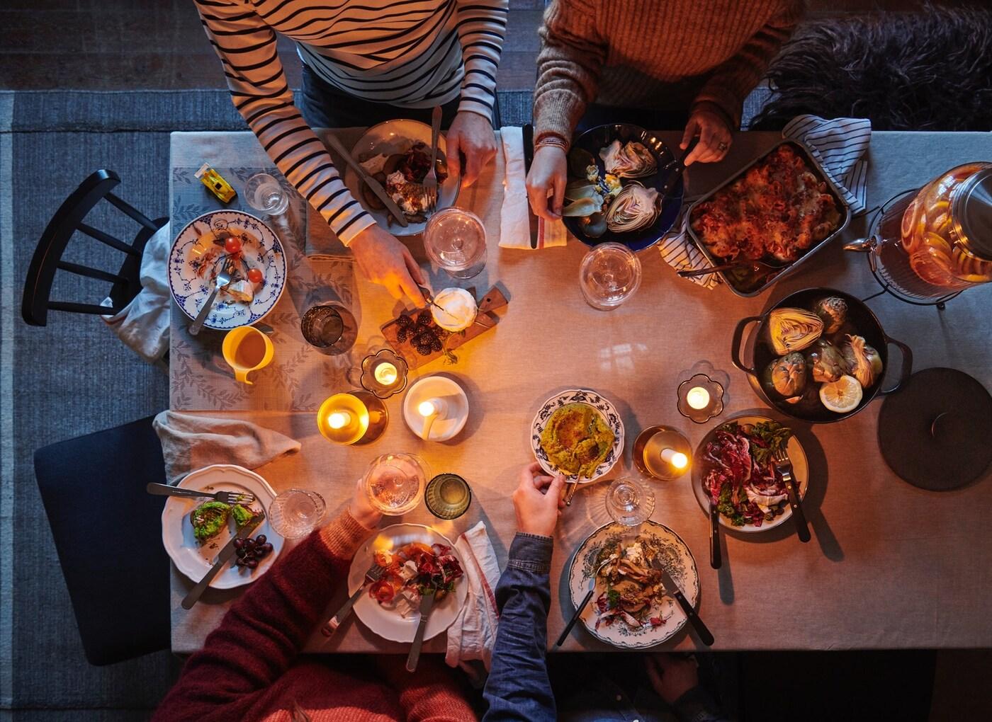 Blick von oben auf einen gedeckten Tisch mit einfarbiger Tischdecke, bunt gemischtem Geschirr und verschiedenen Kerzen