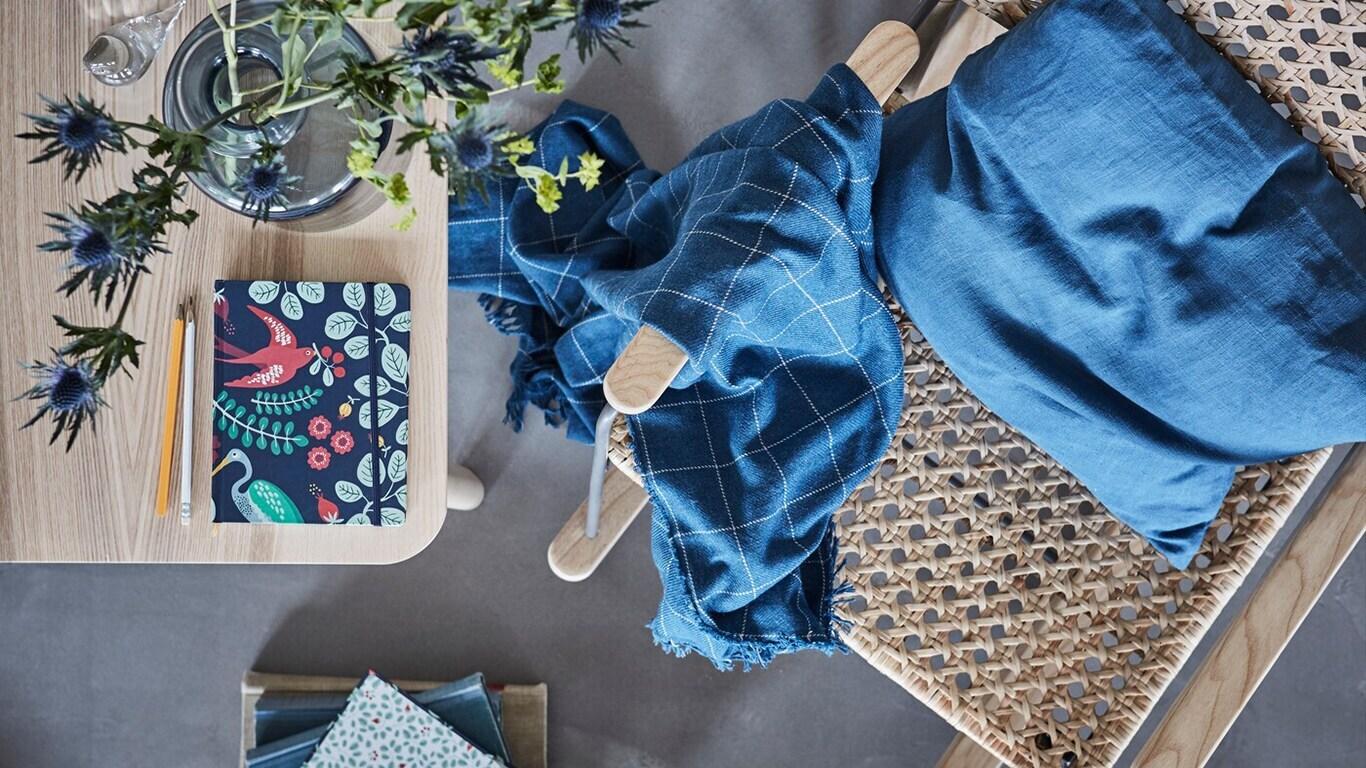 Blick von oben auf einen Rattanstuhl mit blauem Kissen & Decke neben einem Holztisch