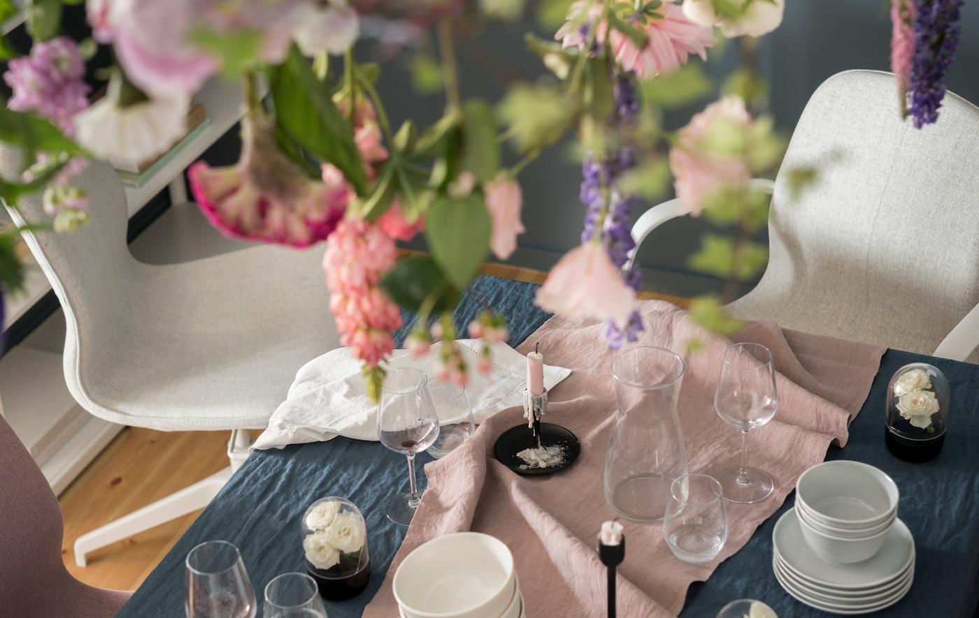 Blick von oben auf weiße Drehstühle an einem blau-rosa gedeckten Esszimmertisch