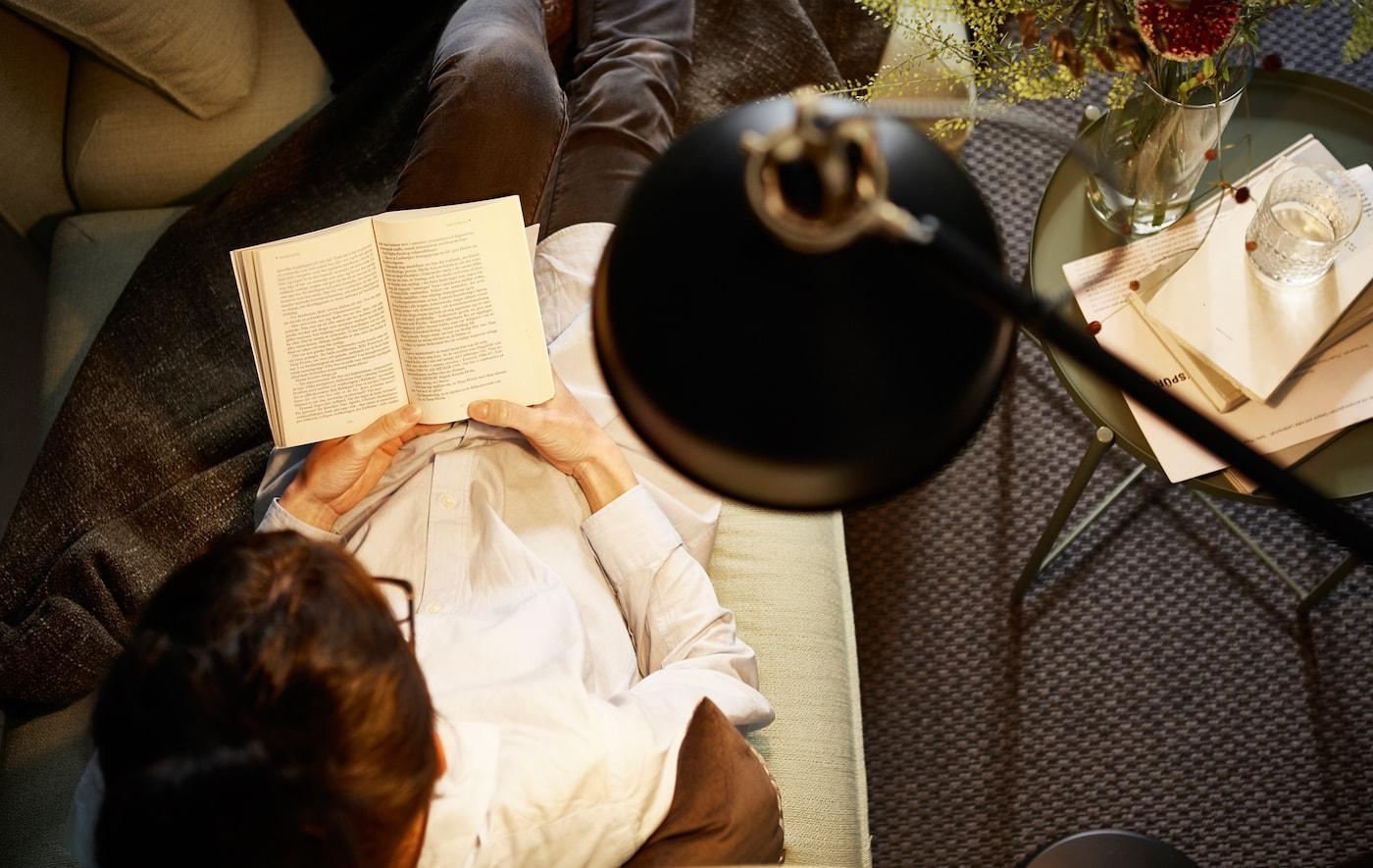 Blick von über einer Leseleuchte auf eine Frau, die auf dem Sofa sitzend liest