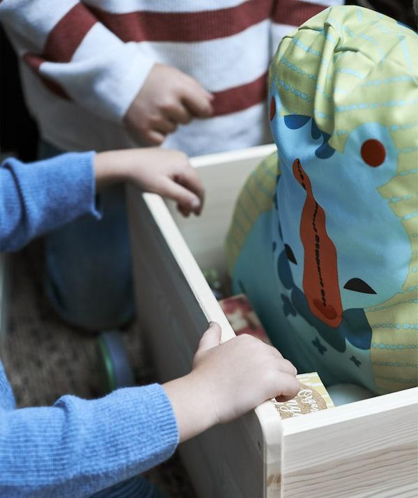 Bliski prikaz dječjih ruku u drvenoj kutiji koja sadrži plišanu igračku.