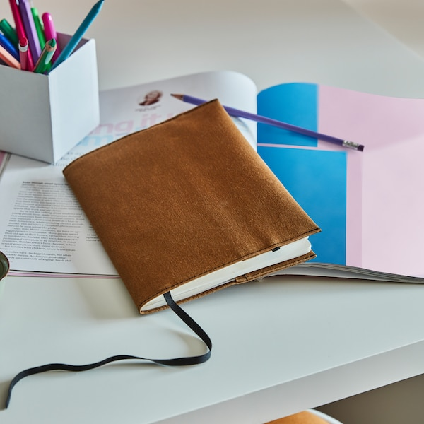 Bloc de notas protegido con funda LANKMOJ marrón, colocado sobre una mesa con otros cuadernos, lápices y bolígrafos.