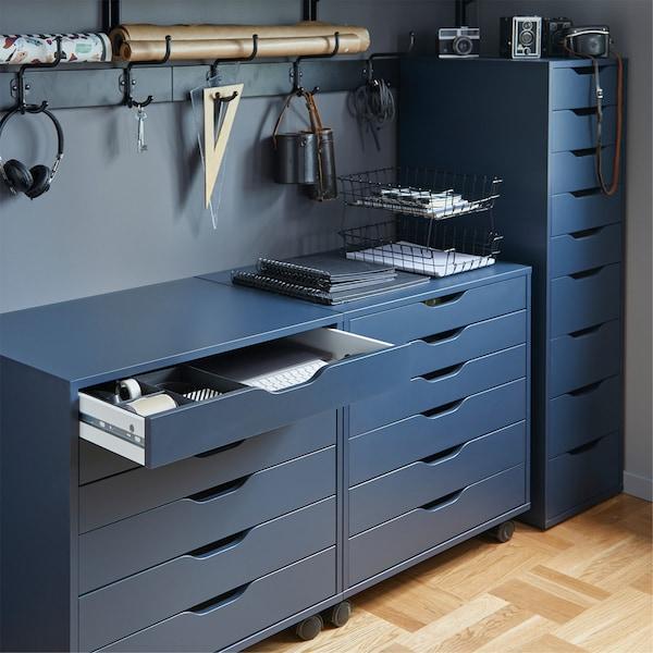 Bloco de gavetas com rodízios ALEX em azul, com uma gaveta aberta e vários artigos de escritório pendurados na parede de trás.