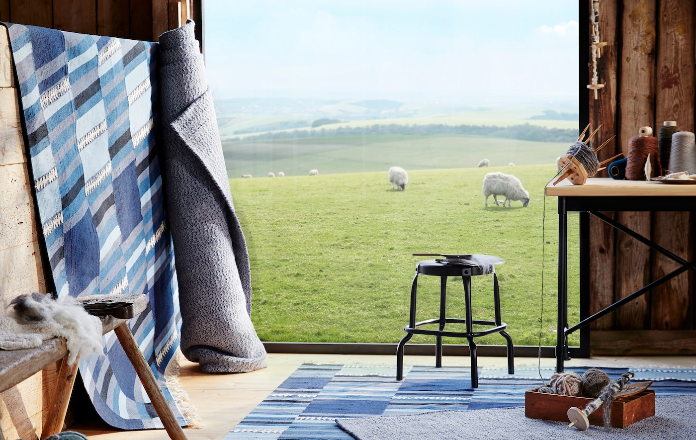 Blue and grey rugs laid out and rolled up in a wooden room, looking out onto a field of sheep.