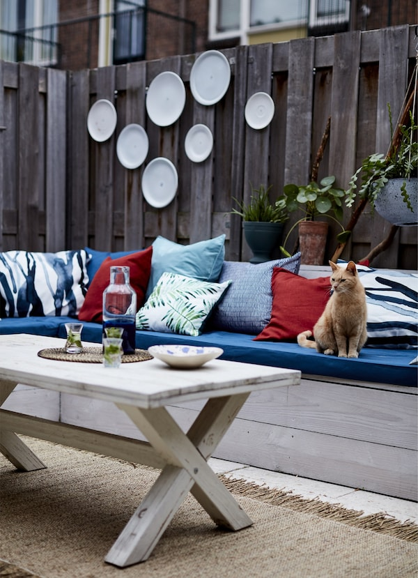Blue and red cushions along a wooden bench.