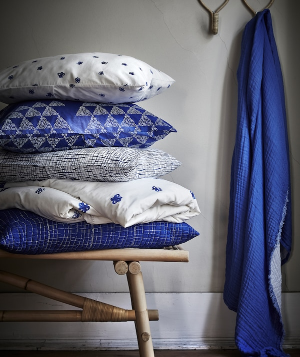 Blue and white patterned TÄNKVÄRD cushions piled up on a rattan bench and blue fabric hanging from a hook.