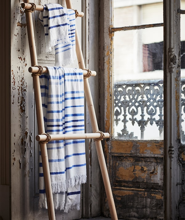 Blue and white striped TÄNKVÄRD fabric hanging on a wooden ladder shelf leaning against a wall.