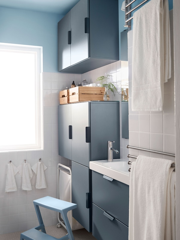 Blue bathroom cabinets that use the whole space from floor to ceiling to maximise storage.