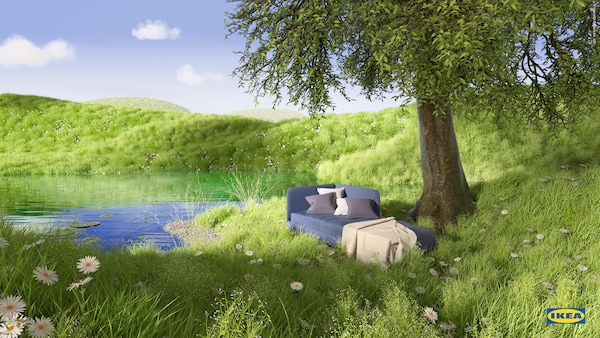 Blue BLÅKULLEN bed frame with corner headboard, a throw and cushions on top, rests in lush green grass by a pond and a tree.