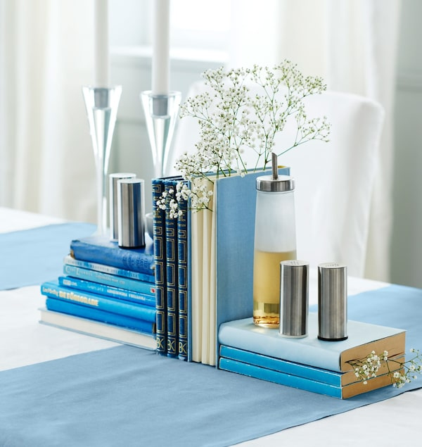Blue books are arranged with candles, baby's breath flowers, salt and pepper shakers, and oil to create a centrepiece.