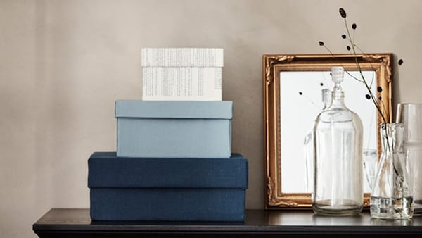 Blue boxes close to a mirror and bottles.