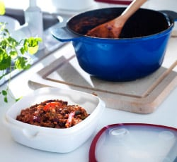 Blue cooking pot and plastic food container on a sunlit kitchen counter.
