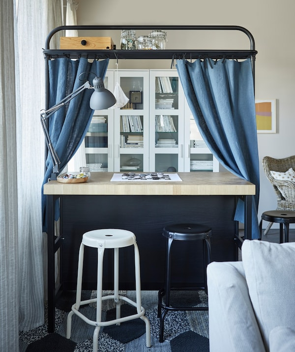 Blue curtains added to the overhead frame on a kitchen island, with RÅSKOG bar stools in front of it.