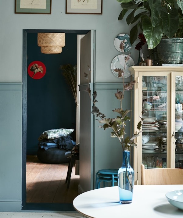 Blue glass vase on a table with view into the bedroom through an open door.