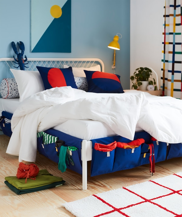Blue MÖJLIGHET textile bed pockets used as storage for socks, suspenders and more, hung on the sides of a bed.