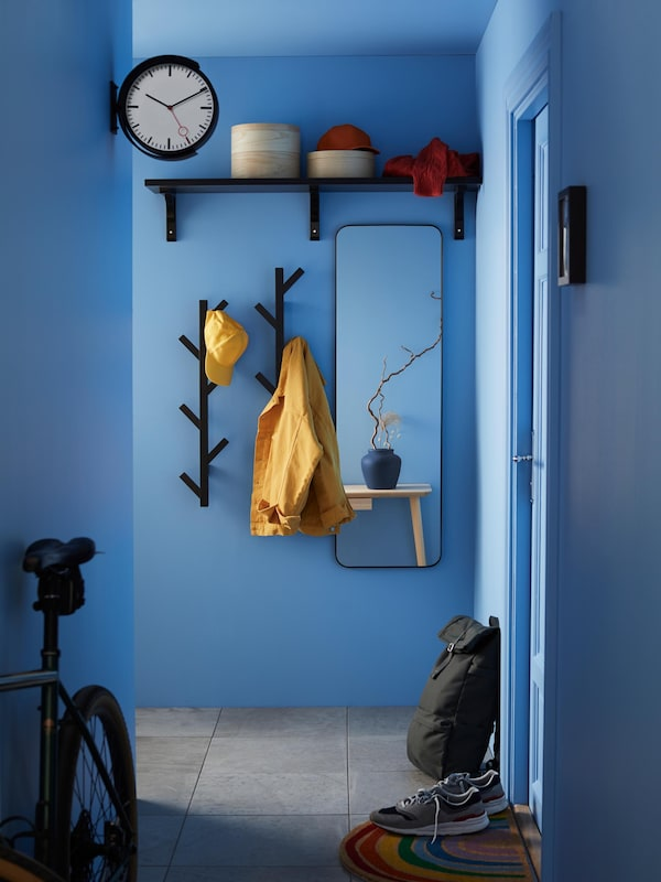 Blue-painted hallway with a large mirror and two vertical racks holding yellow outerwear.