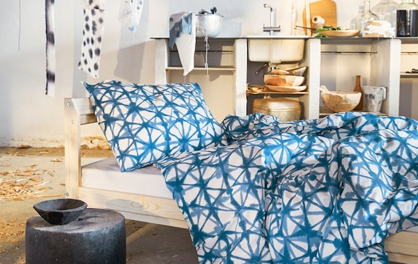 Blue patterned bedding on a bed with wooden frame in a room with open shelves and a sink.