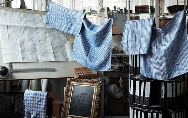 Blue patterned linen hanging on a line in a workshop.