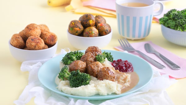 Blue plate with meatballs, mashed potatoes and broccoli with two side bowls of vegetarian and salmon balls.