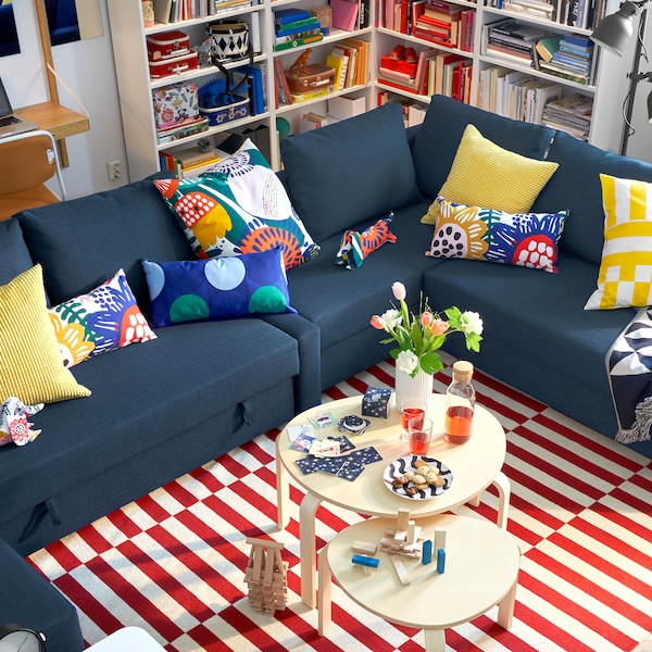 Blue sofa with colorful pillows and a bright yellow cushion.