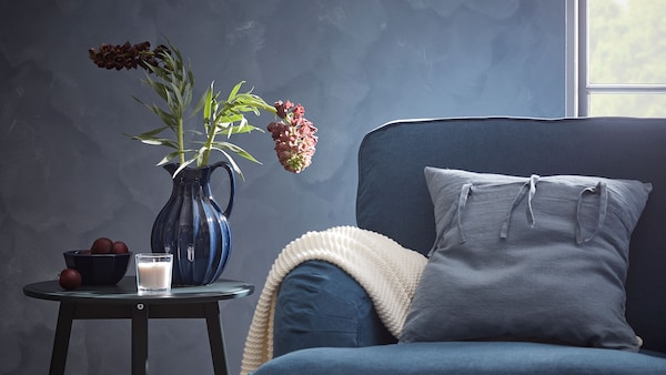 Blue sofa with coordinated accessories and a plant on a side table.