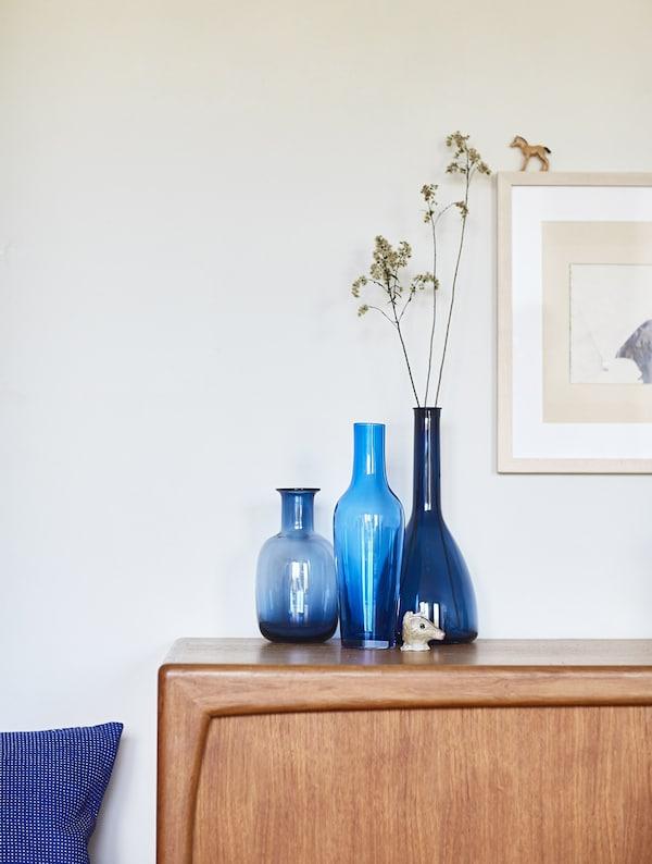 Blue vases on a wooden sideboard.