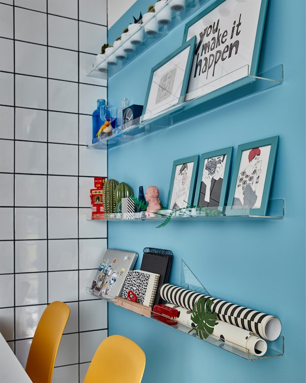Blue wall with transparent picture ledges with blue frames, decorative items, a laptop and more. Yellow chairs in front.