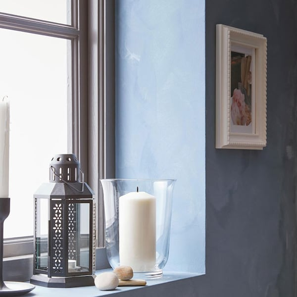 Blue windowsill with a black lantern and tealight, with various candles.