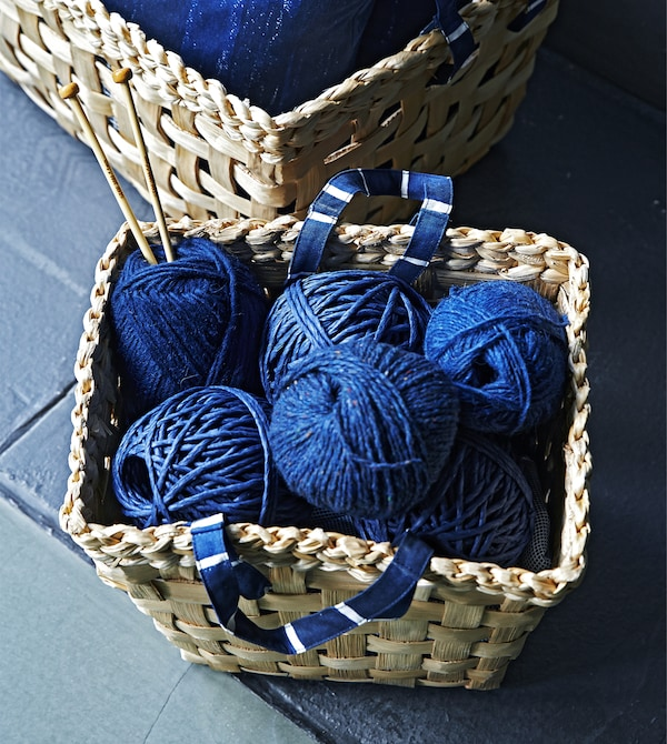 Blue yarn in a woven basket with blue handles.