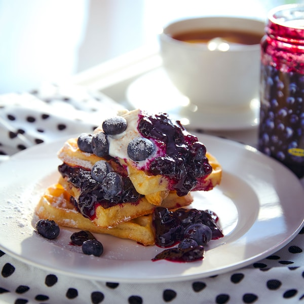 Blueberry jam on a pile of waffles with fruit
