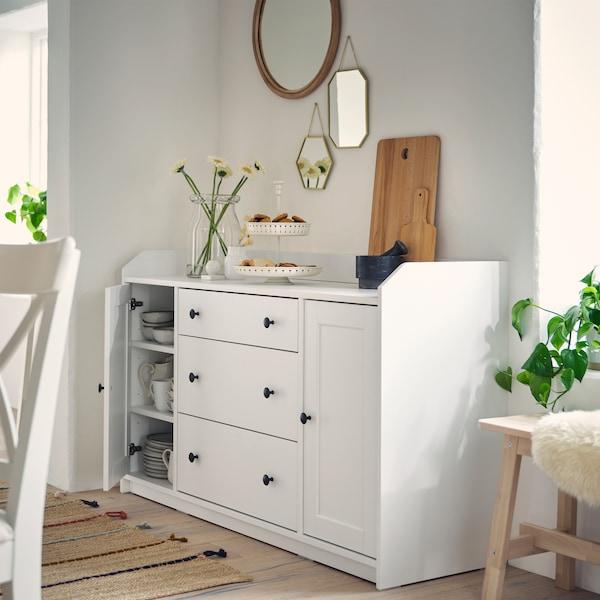 Blumen in einer Vase, eine Etagere mit Gebäck und Schneidebretter befinden sich auf einem weißen Sideboard. Darüber hängen verschiedene Spiegel an der Wand.