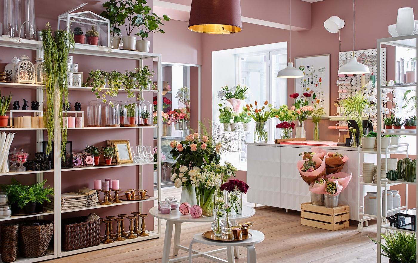 Blumenladen mit rosafarbenen Wänden, FJÄLKINGE Regalen, KRAGSTA Tisch, Dekoartikeln & bunten Blumen.
