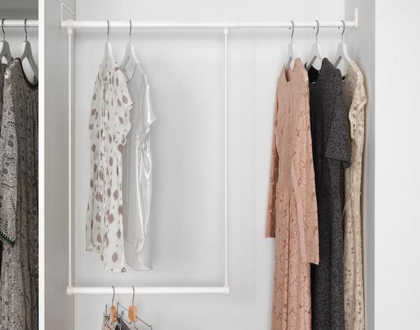 Bluser og kjoler, der hænger på bøjler på en garderobestang i to niveauer, der er sat op mellem et garderobeskab og en væg for at udnytte al plads.