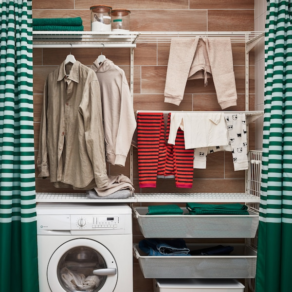 BOAXEL sections with baskets, clothes rails and drying racks are built around a laundry machine and create a laundry area.
