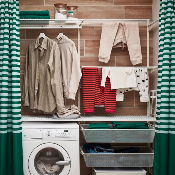 BOAXEL sektioner med korgar, klädstänger och torkställ som placerats runt tvättmaskinen och ger en egen zon för tvätten.