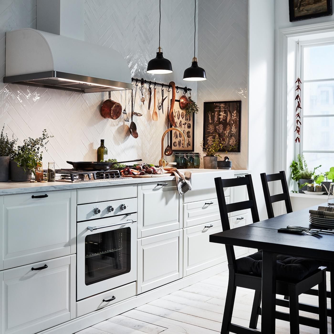 BODBYN kök i off-white lyses upp av två svarta taklampor. Bredvid står ett svart bord och två svarta stolar.