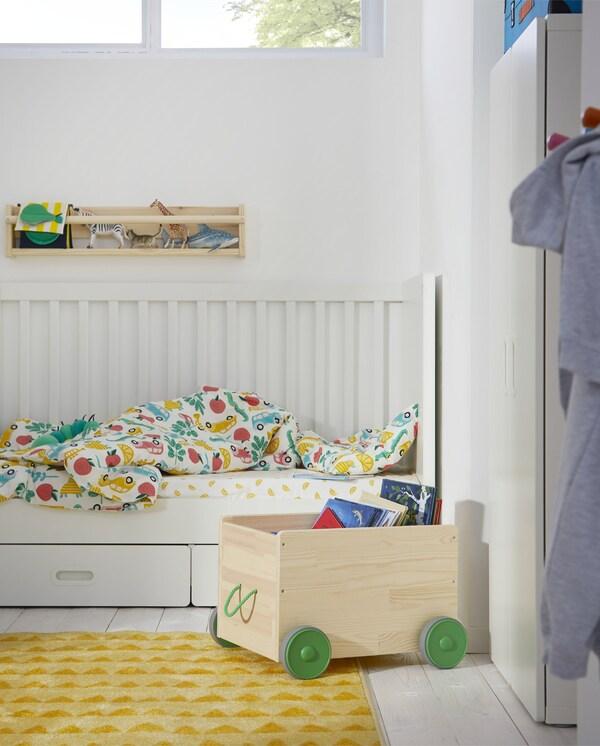 Boeken worden opgeborgen in een FLISAT speelgoedopberger in grenen met wielen en een groene handgreep. De opberger staat naast een wit babybed.