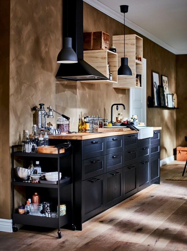 Bohato zariadená kuchyňa s malým otvorenými nástennými skrinkami, kuchynským odsávačom a tmavými čelami zásuviek LERHYTTAN.