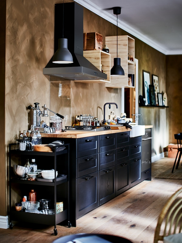 Bohato zariadená kuchyňa s malými otvorenými nástennými skrinkami, kuchynským ventilátorom a tmavými čelami zásuviek LERHYTTAN.