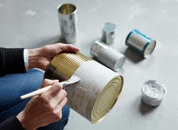 Boîtes de conserve peintes avec une pâte ressemblant à du ciment et transformées en rangements pour la cuisine